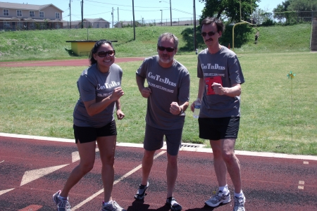 Three people in matching running shirts pose on an outdoor track.