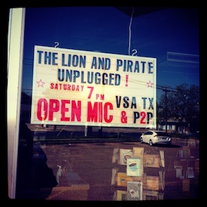 Photographed through a floor-to-ceiling, a marquee reads The Lion and Pirate Unplugged! Saturday 7pm OPEN MIC VSA TX & P2P. The lettering is black and red.