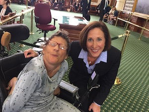 Two women pose for a photo, one sitting in a power chair with her arm tucked behind her, and the other leaning down to be shoulder-to-shoulder with the first.