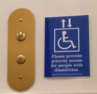 Next to the gold colored up and down buttons of an elevator, a blue sign with a handiman image reads Please provide priority access for people with disabilities.