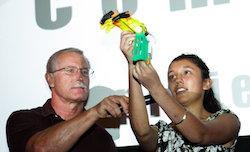 A man holds a microphone up to the face of a young woman who is using both hands to lift up a colorful, plastic prosthetic.