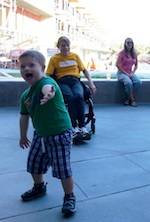 A little boy laughs and reaches his hand toward the camera while a dancer sitting in a wheelchair and spectators sitting farther back look on and smile.