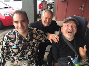 Three men smile at the camera, two sitting in wheelchairs and the third kneeling behind them.