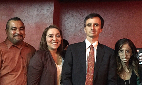 Four people stand close together in a line, all smiling broadly at the camera.