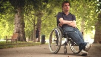 Under the shade of trees, a man sits back in his wheelchair, crossing his ankles and arms, with an unamused expression on his face.