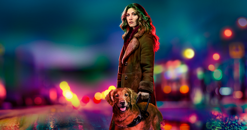 A woman with a golden retriever looks out somberly from a background of blurred, colorful city lights.
