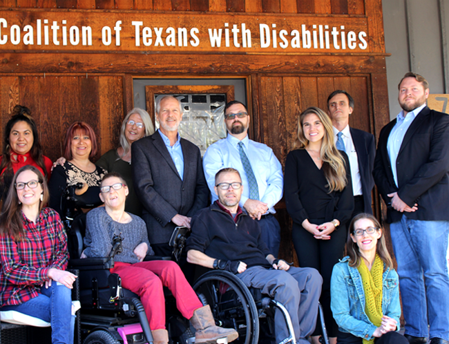 Relaxed staff photo. A group of eleven smiling men and women in business casual dress sit or stand in two rows on a large front porch with wood panelling. The words Coalition of Texans with Disabilities appear in bright white over the door behind them.
