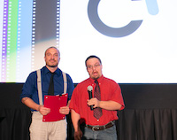 Garret, in a bright red shirt and tie, appears to be making a serious statement into the microphone he's holding. Beside him, Orion holds a folder with both hands and looks out into the audience with a wistful expression.