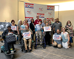 A group of about 20 people with various disabilities stand, sit, and kneel in front of a REV UP banner, some holding signs that read Vote!
