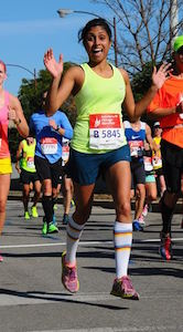 A woman in running clothes in mid-stride waves both hands at the camera and smiles enthusiastically.