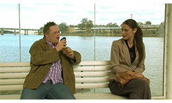 A man speaking into a tape recorder lounges on a bench, while the woman sitting next to him seems intrigued but hesitant.