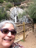 A woman in sunglasses smiles from the bottom corner of the frame. A wooden fence and waterfall are directly behind her.