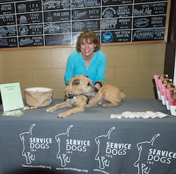 On a display table with brochures and a basket, a woman smiles broadly and leans over a sandy colored dog, who is looking to the right.