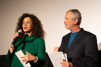 A woman with an adamant expression speaks into a microphone while a man next to her listens somberly.