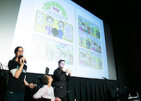 A comic book spread is projected onto the theater screen. A woman in the foreground speaks into a microphone, a woman seated next to her looks up at the screen, and a man next to then signs ASL.