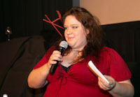 A woman holding index cards in one hand speaks into the microphone she is holding with the other.