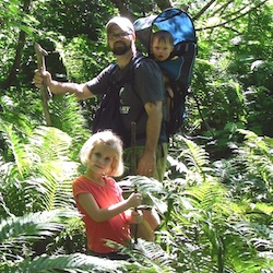 A family of three- a father with a baby strapped to his back and a little girl in the foreground- pose in a lush forest setting.