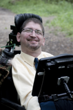 A man in a power chair equipped with a screen grins at the camera.