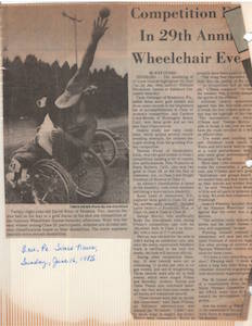 Newspaper clipping of an article titled 29th Annual Wheelchair Event. In the photo, a muscular male shot-putter in a wheelchair twists to one side and reaches one arm over his head, heaving an iron ball into the air.