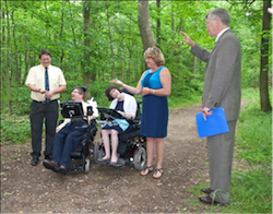 A group of 5 formally dressed people stand/ sit in the middle of a wooded area.