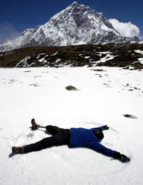 On snow-covered ground, with a mountain peak in the background, a warmly-dressed man with a prosthetic leg makes a snow angle.