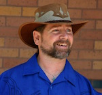In front of a brown brick wall, a bearded man in a blue collared shirt and cowboy hat smiles in amusement at something off camera.