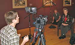 A woman in a western shirt sits in a chair and gazes off camera, while a young man in the fore-ground looks into the viewing screen of a video camera.