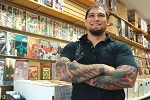 In front of a wall of comic books, a man crosses his tattooed arms and appears to be laughing at something off camera.