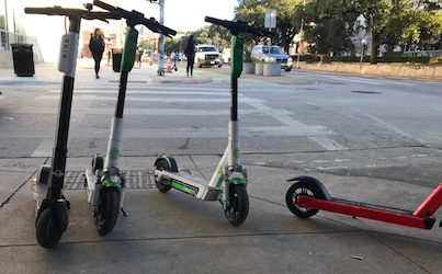 4 electric scooters stand in the middle of a curb cut, blocking the path to a crosswalk.