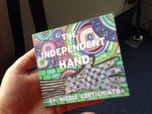 A hand holds up a book with a colorful cover in a hand drawn style to the camera. It reads The Independent Hand by Nicole Cortichiato.