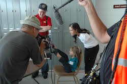 A film crew surrounds a young girl in profile with no arms, sitting back in a chair, feet to an airplane steering device. Jessica Cox, also without arms, standing, bends down behind her and smiles.