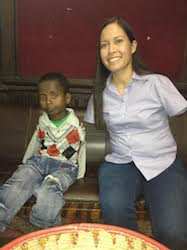 A young boy and a woman, Jessica Cox, both without arms, sit on a black bench. She smiles readily at the camera, his expression is more hesitant.