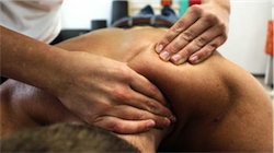 Close up on a pair of hands massaging the neck and shoulder of a person laying face down.
