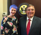 A woman with short periwinkle hair stands shoulder to shoulder with an older man in a suit. A US House of Representative seal is hung behind them.