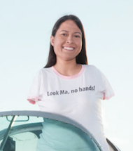 Jessica Cox, a young woman with no arms, stands up behind a windshield. She wears a shirt that reads, Look Ma, no hands!