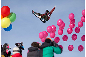 A snowboarder soars over a crowd of photographers and colorful balloons.