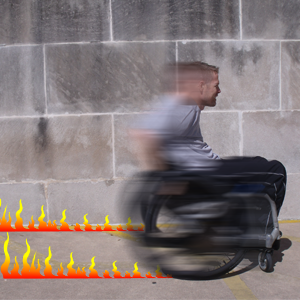 Viewed in profile, a man races by in a wheelchair, blurred and leaving a trail of flames.