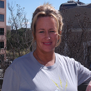 A woman in a Lightning Laces running shirt smiles at the camera.