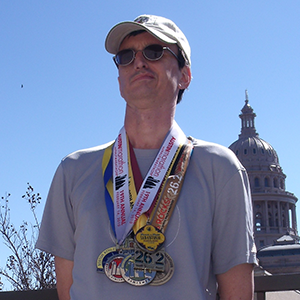 A man in a baseball cap and sunglasses gazes past the camera. He wears about 15 racing medals around his neck.