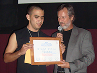 An older man speaking into a microphone hands a certificate to a younger man whose eyes are closed.