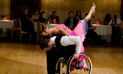 A man in a tuxedo bends forward in his wheelchair while a woman in a formal gown lays on his back with a leg in the air.