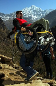 With a snow capped mountain in the back ground, two men ascend a rocky path. One is leaning back in a push wheelchair, strapped by a yellow cord to the back of the other.