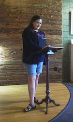 In a wood paneled corner resembling a stage, a woman reads off a podium.