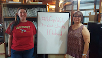 Two women stand on either side of a whiteboard that reads #NoCapsNoCuts to our clients' Medicaid. In the background is a large bookcase full of files.