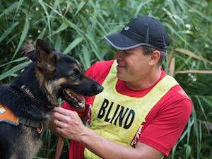 Amid tall blades of grass, a smiling man with a cap and yellow vest that reads Blind adjusts the collar of a panting German Shepherd.