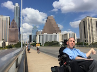 A man in a power chair rolls across a sidewalk with Austin's skyline and a bright blue sky behind him.