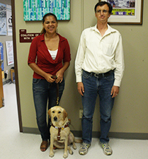 A young woman with a blond guide dog and a tall man smile at the camera