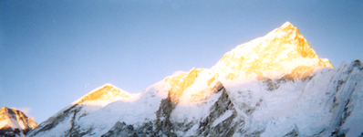 A wide photo of snow-capped mountain peaks, with bright sun shining off the very top.