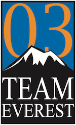 A simplified graphic of a black and white snow-capped mountain on a blue background. 03 appears in orange behind the mountain and Team Everest in white below it.