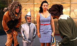 People dressed as variations of the Lion, the Tin Woman, and Dorothy from the Wizard of Oz stare with varying levels of dismay at a piecemeal ScareCrow.